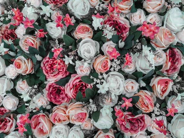 カラフルな造花の壁の背景のクローズアップ。バラの花の壁紙の背景。