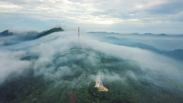 美しい霧と山の上の空撮テレビ送信局