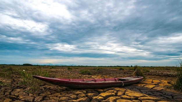日の出と干ばつ土地の上の木造船