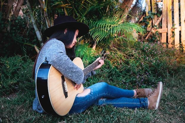 流行に敏感な若い女性の庭でギターを弾く