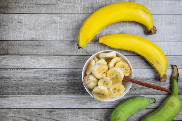 新鮮なバナナとバナナをテーブルの上の健康のためにボウルに細かく刻みます。