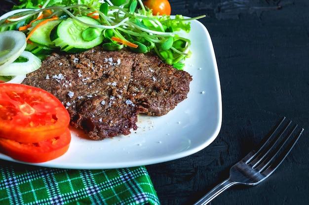 牛肉のグリルステーキとテーブルの上のヘルシーサラダ