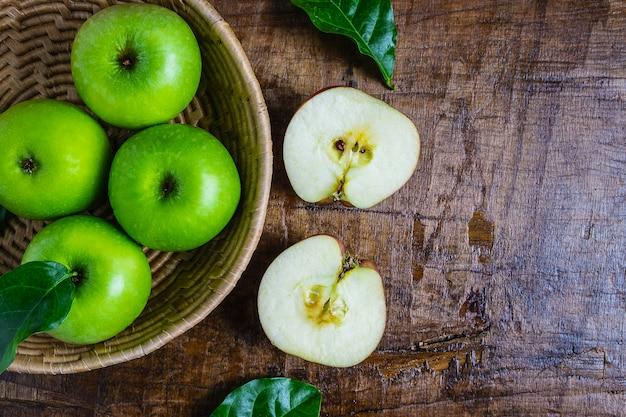木製のテーブルの上のバスケットに青リンゴ
