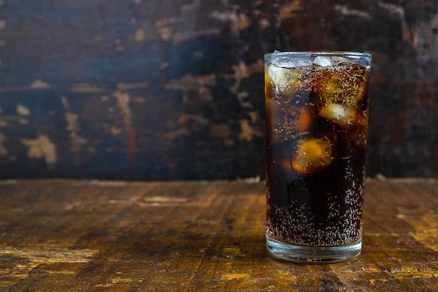 Кола напиток, черные безалкогольные напитки в стакане на столе