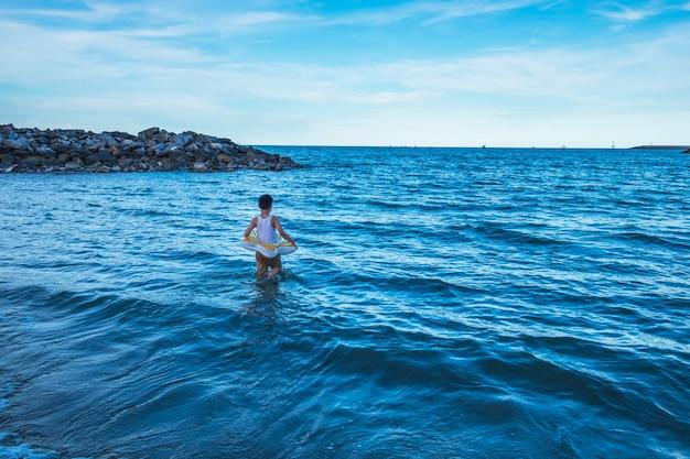 強く立ちなさい。海の波の真ん中に立っている少年