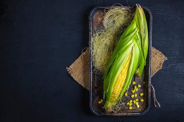 黒の背景上のトレイに新鮮なトウモロコシ