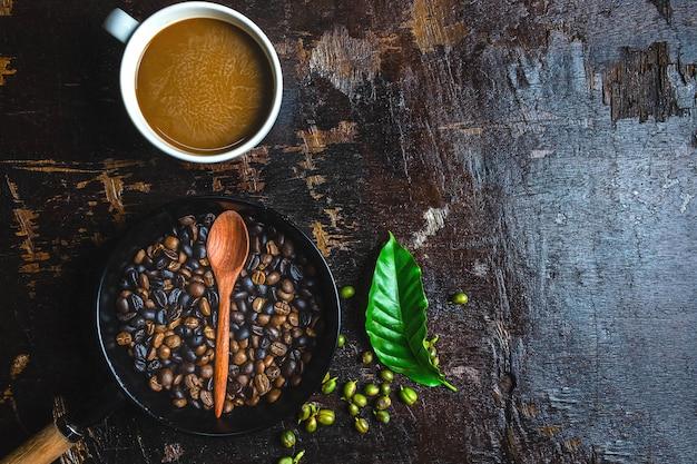 一杯のコーヒーと木製のテーブルの上のコーヒー豆