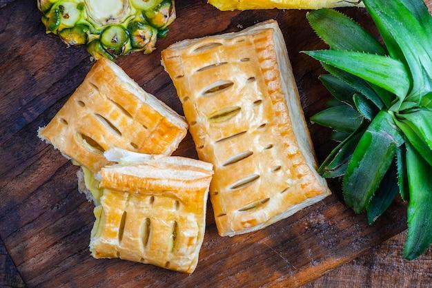木製の背景にパイナップルパイとパイナップルフルーツ