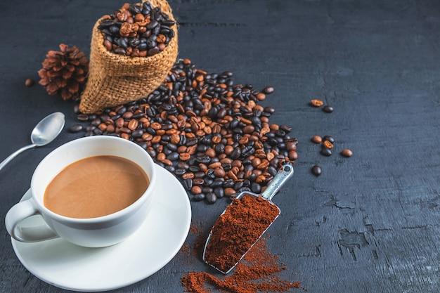 テーブルの上のコーヒーカップと焙煎コーヒー豆と挽いたコーヒーパウダーのコーヒー