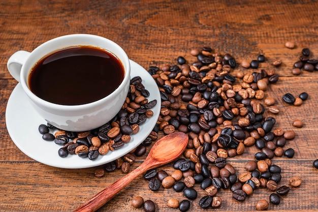 コーヒーカップと木製のテーブルの上のコーヒー豆