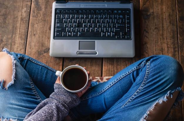 オンラインでの作業と一杯のコーヒーに座っている若いビジネス女性