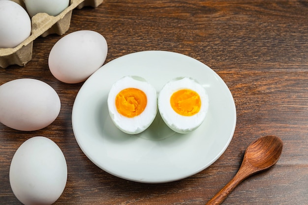 Белые утиные яйца и соленое яйцо на деревянном столе