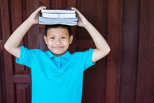 Мальчик держит учебник на голове.
