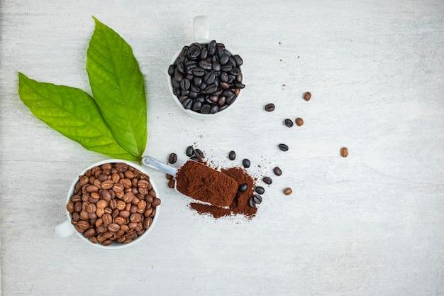 コーヒーパウダーと白いテーブルの上のコーヒー豆