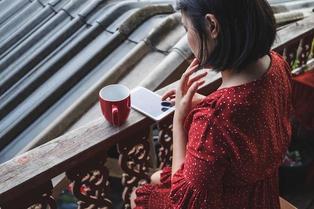 テラスでコーヒーの上に座ってライフスタイルの女性