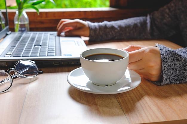女性は働き、コーヒーを飲む