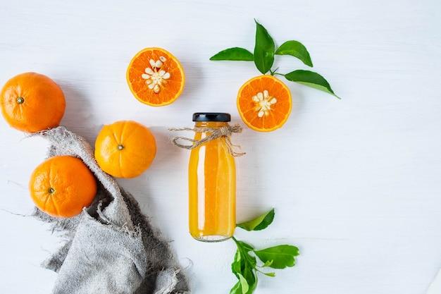 新鮮な柑橘系の果物と絞りたてのオレンジジュースのボトル