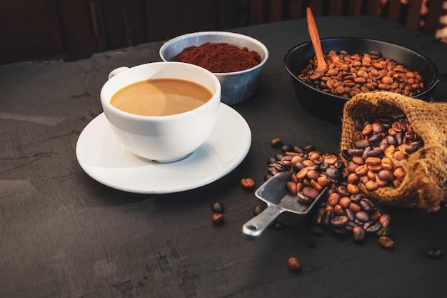 コーヒーカップと黒いテーブルの上の豆。上面図