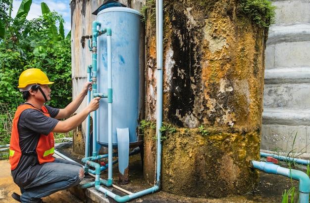 配管工は水タンクと水フィルターを修理しています。