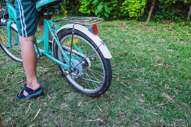 アジアの少年は自転車をこいでいます。