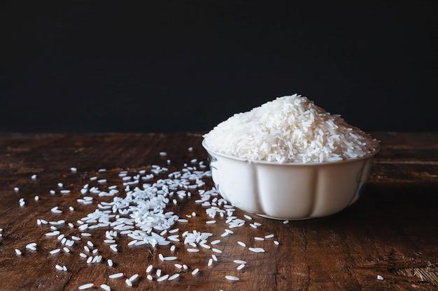 木製のテーブルの上にボウルに白い生米