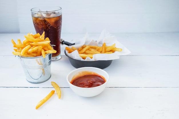 Жареный картофель фри и кетчуп с безалкогольными напитками на столе