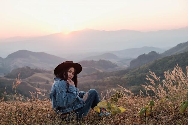 Красивая женщина сидит и наслаждается видом на горы