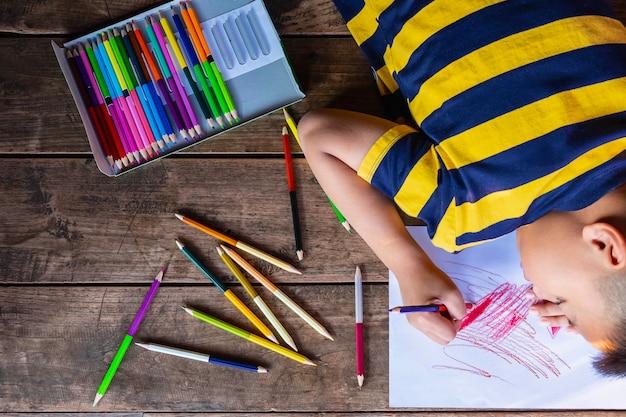 Мальчик рисует на белой бумаге с цвет дерева