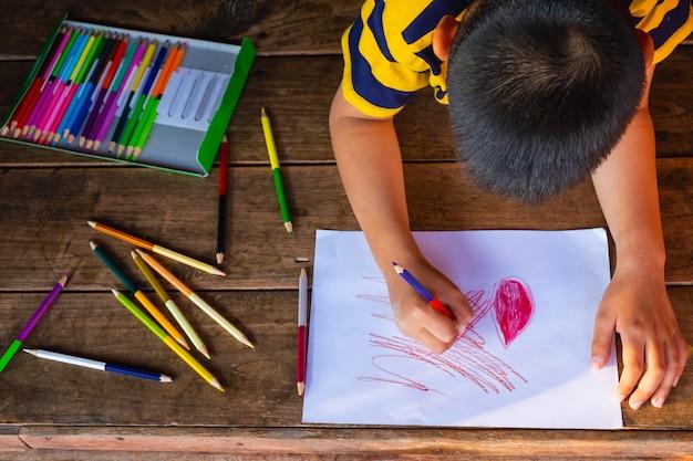 Мальчик нарисовал на белой бумаге цвет дерева