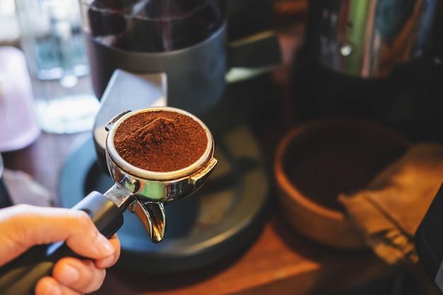 Бариста прессует молотый кофе, используя тампер
