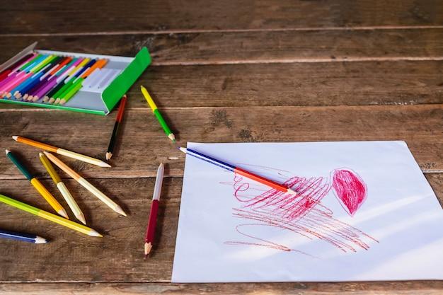 白い紙と木製の色鉛筆で絵を描く