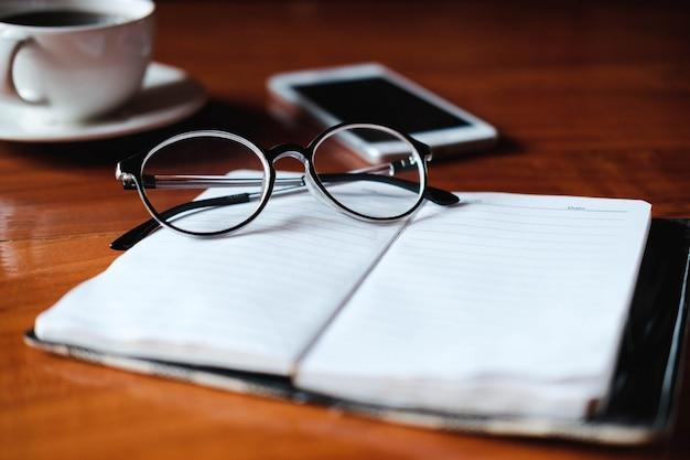 ノートブックのメガネ、机の上のコーヒーカップ