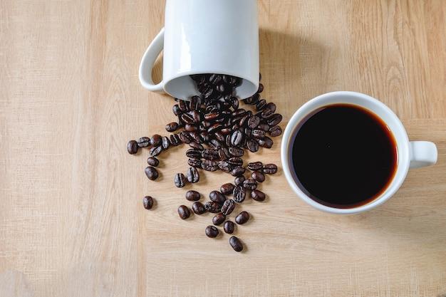 木製のテーブル上のコーヒーカップでコーヒーとコーヒー豆
