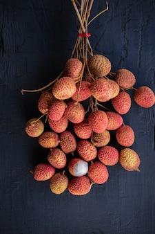 Свежие фрукты личи на черном деревянном столе