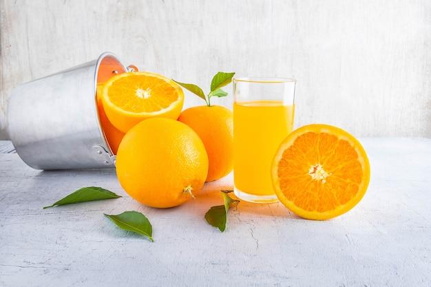 新鮮なオレンジジュースと白い木製の背景にバスケットにオレンジ。