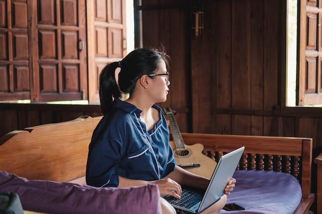 若い女性が自宅のラップトップでソファに座って作業