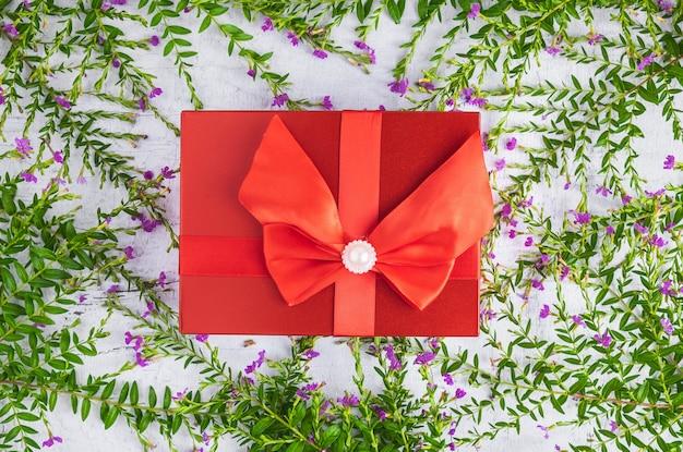 Красный фон подарочной коробки и листья