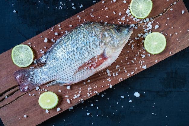 木製のチョッピングボードにティラピアの新鮮な魚