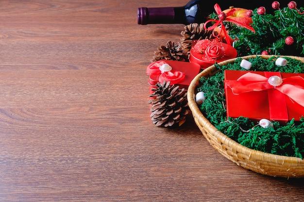 クリスマスとお祝いのドリンクのバスケットに赤いギフトボックス
