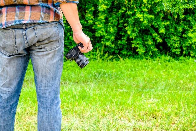 フォトグラファーは、写真を準備するためにカメラを持って立っています。