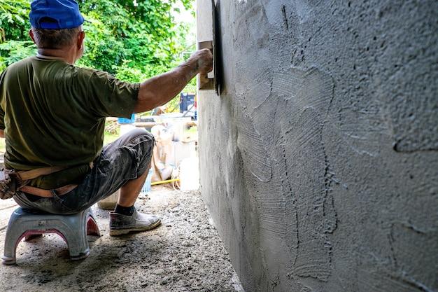 労働者は石膏の壁に取り組んでいます。