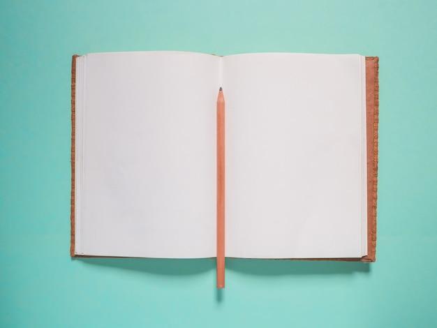 Блокнот и карандаш на зеленом фоне