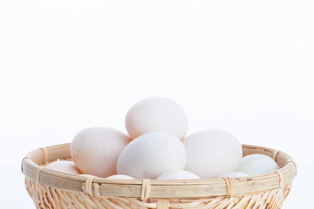 白い背景に竹のボウルのバスケットで生の汚れたアヒルの卵