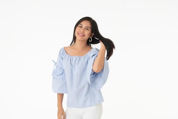 Молодая женщина портрета азиатская использует ее руку касается ее изолированным волосам