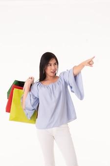 分離された買い物袋を運ぶ幸せなアジアの若い女性