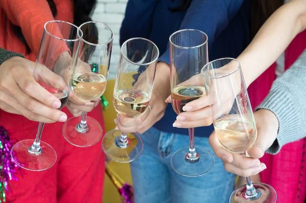 クリスマスパーティーの時間。シャンパンフルートで乾杯する若いアジア人。お友達と新年をお祝いします。