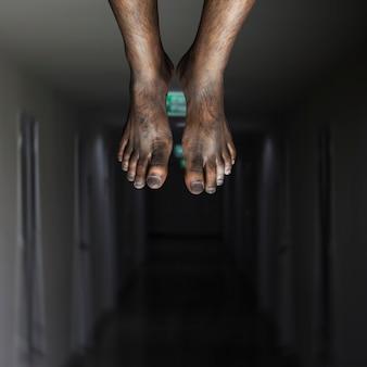脚が暗い背景にぶら下がっていた