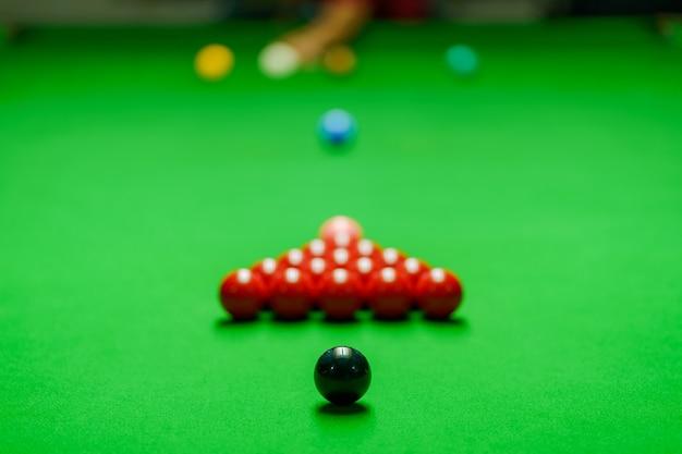 プレイヤーは緑色のスヌーカーテーブルでボールを撃っていた