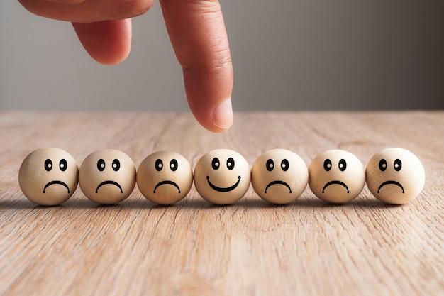 笑顔の木製のボールを指す手、募集の概念
