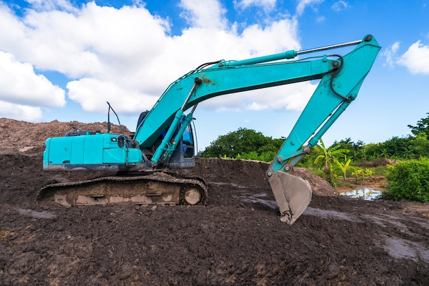 青空の下で建設現場の掘削機
